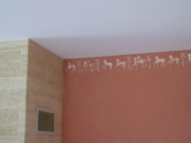 """décor avec une frise décorative """"style antique"""" sur un haut de mur dans une salle à manger"""
