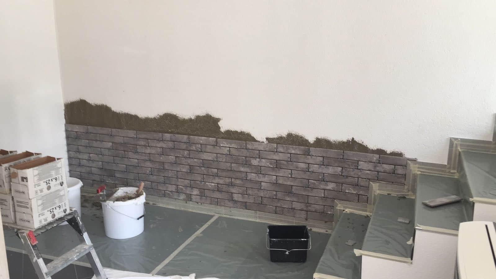 Pose au mortier de pierres de parement sur un mur dans une salle à manger