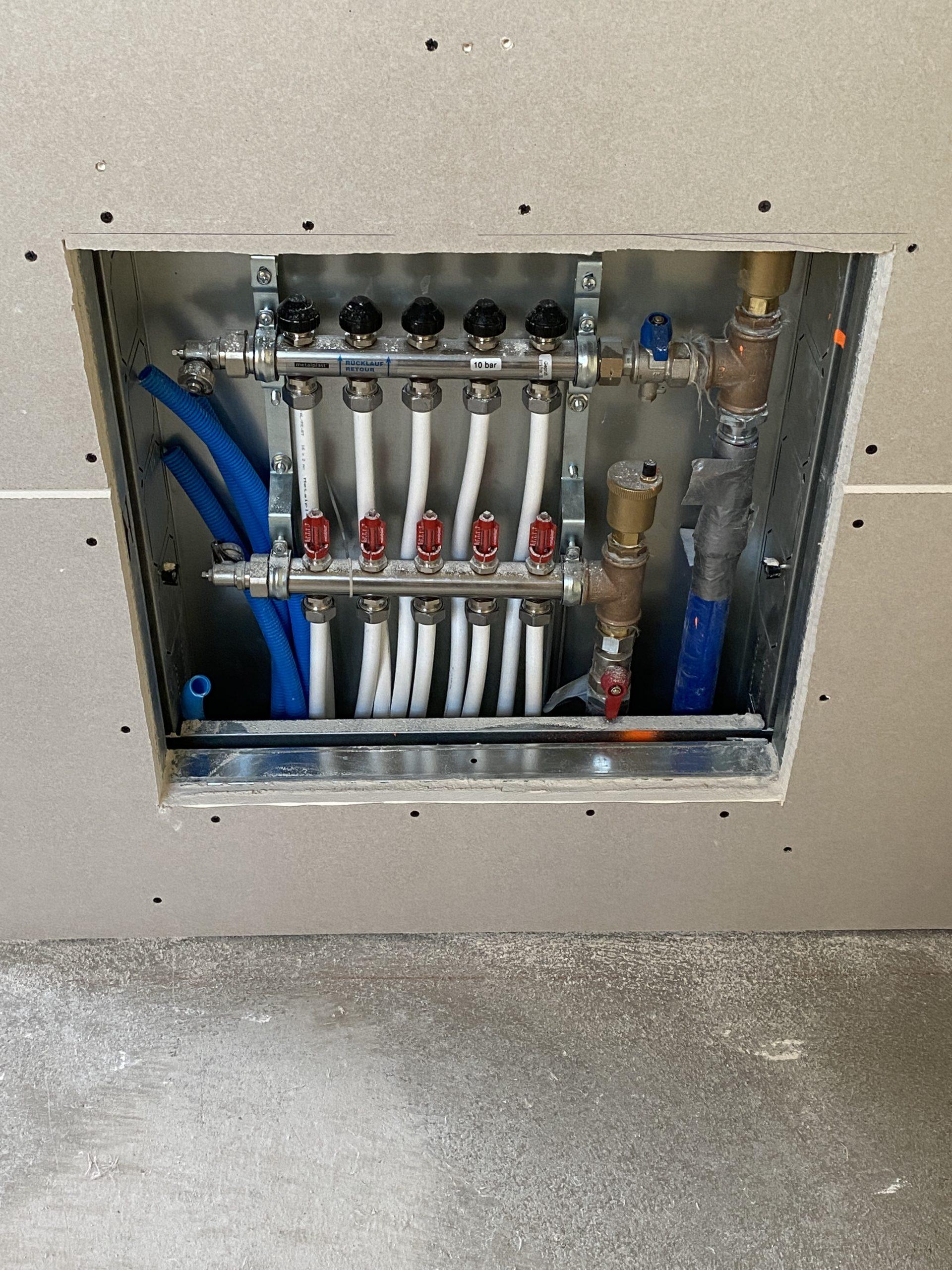 Montage de plaques de plâtre cartonnées sur une ossature métallique pour cacher un collecteur de chauffage par le sol